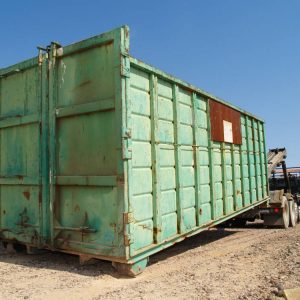A big green dumpster being delivered to a construction site in Arizona.